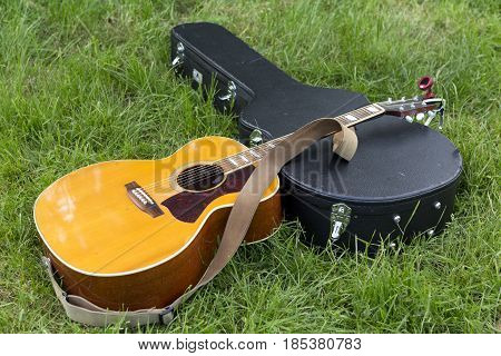 An acoustic guitar resting on it's case on the ground
