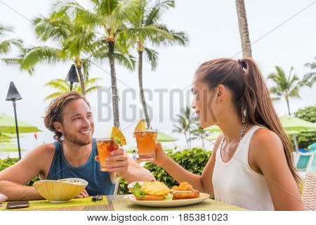 Couple eating at hotel restaurant on Hawaii travel vacation beach drinking hawaiian drink mai tai. Happy people toasting cheers with cocktails. Summer holidays at resort.
