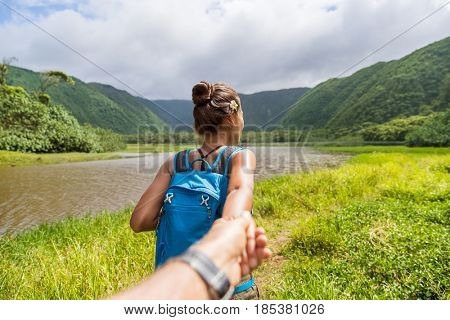 Hawaii travel nature hiker follow me woman hiking in Pololu valley holding hand of boyfriend following leading girlfriend walking. Big island destination, woman tourist in Hawaii, USA.