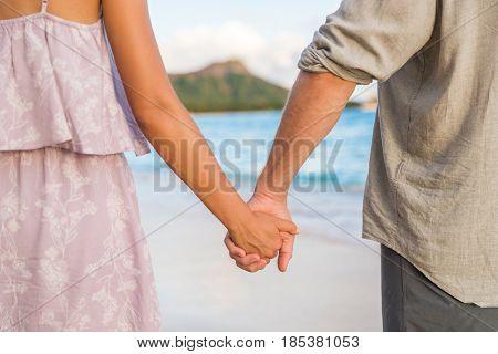 Honeymoon travel beach vacation couple holding hands in sunset. Newlyweds in love. Waikiki beach in Honolulu, Hawaii.