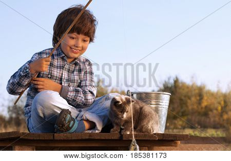 Happy boy go fishing on the river with pet, one children and kitten of the fisher with a fishing rod on the shore of the lake