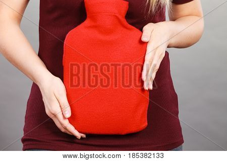 Woman holding in hand warm hot water bottle in red soft fleece cover on grey. Health care pain relievers treatment objects concept.