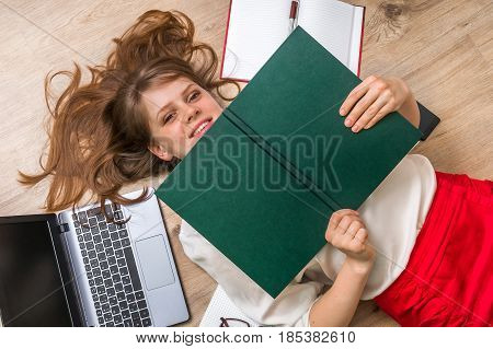 Woman Lying On Back And Covering Her Face With Book