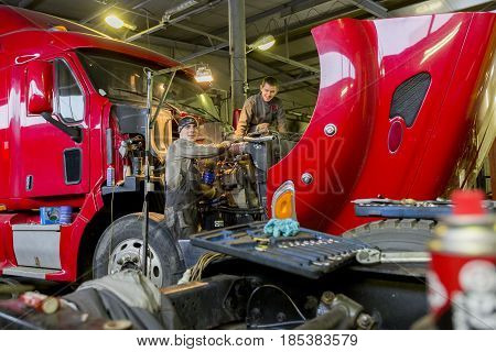 Nizhny Novgorod, RUSSIA - MARCH 19, 2017: Workers car mechanics make repairs of trucks in the indoor hangar. Russia.