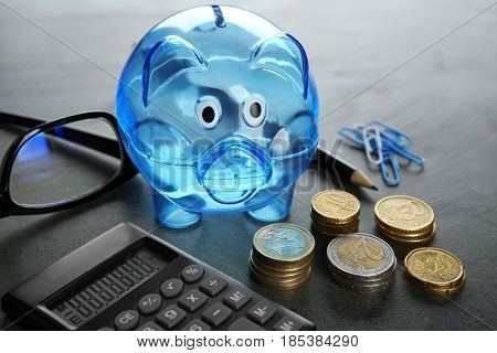 Composition of piggy bank, coins and calculator on grey table