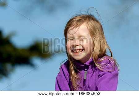 portrait of a little girl in a lilac jacket on a blue sky background on a sunny day, the child laughs and closed his eyes, a wide smile