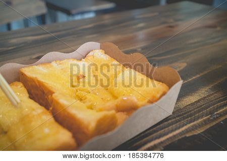 Toast bread with sweetened condensed milk on wood table.