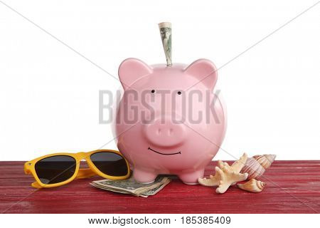 Pink piggy bank with money, sunglasses, starfishes and shells on wooden table