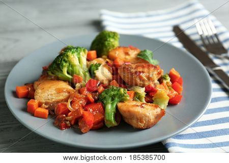 Chicken stir fry with vegetables and cutlery on table