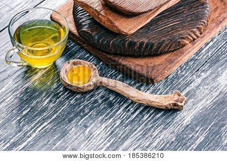Green tea in translucent glass tea cup with honey and wooden tableware on textured black wood background