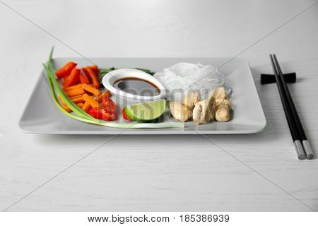 White plate with delicious rice noodle and vegetables on wooden table