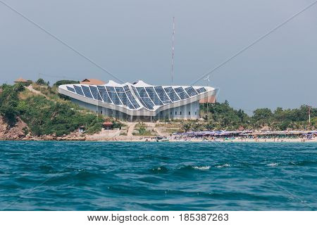 Chonburi, Thailand - November 2, 2012: Front View of Samae Beach in Ko Lan near Pattaya City. With Stingray-Shaped Building and Tourists on the Beach.