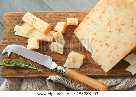 Cutting board with cheese and special knife on wooden background