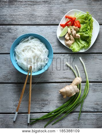 Plates of tasty rice noodles and vegetables on wooden table