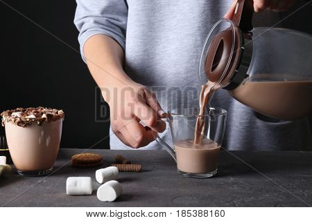 Young woman pouring cocoa drink into cup on black background, closeup