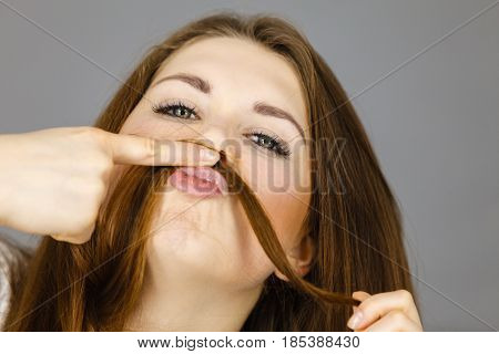 Woman having fun with her long brown hair making moustache being happy about hairdo condition studio shot grey background.