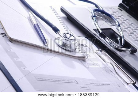 Medical stethoscope , laptop, folder on the desk