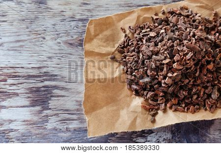 Heap of aromatic cocoa nibs on wooden table