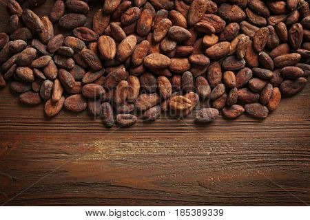 Aromatic cocoa beans on wooden background