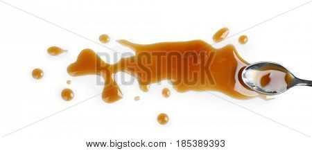 Delicious caramel sauce on white background with spoon
