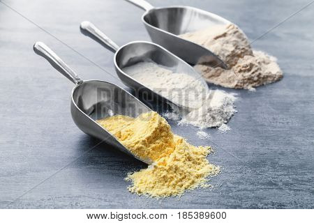 Scoops with different types of flour on wooden background, closeup