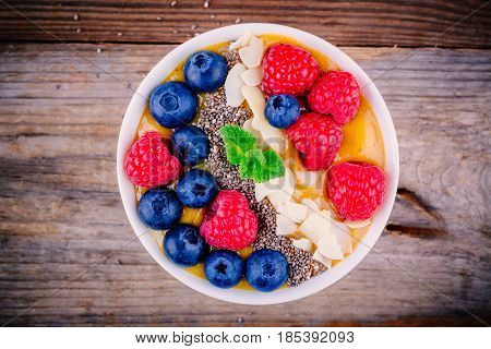 Peach Smoothie Bowl With Raspberries, Blueberries, Chia Seeds And Almonds