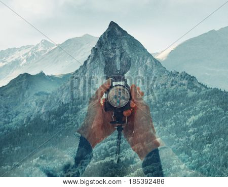 Double exposure image of mountain and female hands with hiking compass.