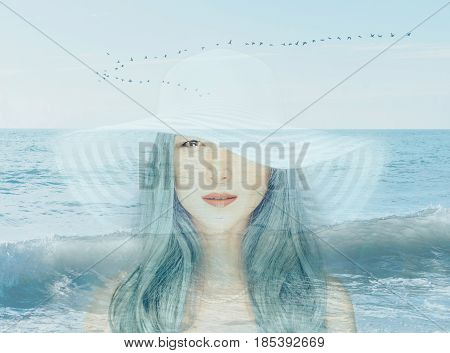 Double exposure portrait of beautiful young woman with blue hair combined with image of seascape.