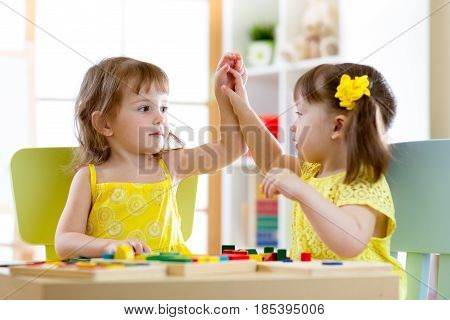 Two children little girls playing together in daycare