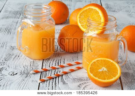 Detox Water With Oranges In A Mason Jar With Straw. Downward View On Wood With Checkered Cloth.