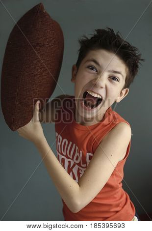 teenager mischivous boy fighting with pillow open mouth close up portrait