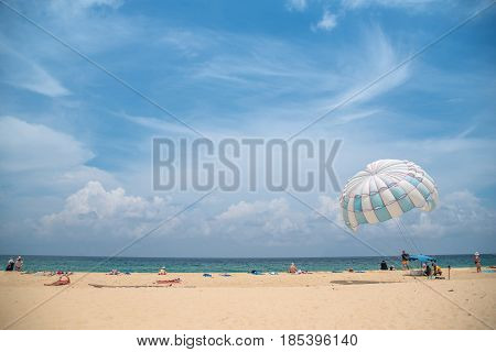 Tourists and parasailing on tropical beach against beautiful blue sky background or backdrop for summer holiday and vacation travel concepts