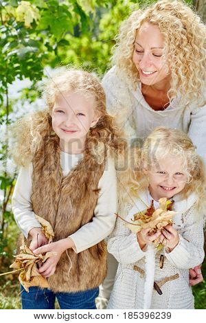 Family with two childern and mother collecting leaves in the nature