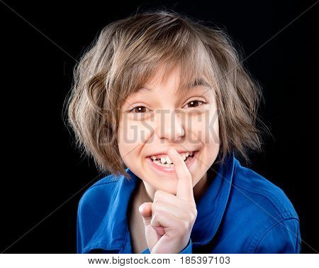 Emotional portrait of attractive caucasian little girl with finger up to lips for making a quiet gesture, on black background. Child showing silence gesture looking at camera.