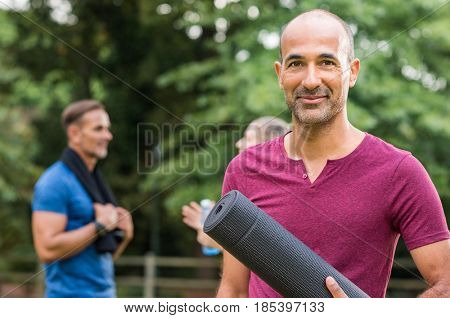 Smiling mature man holding yoga mat and looking at camera. Portrait of a happy mixed race man with yoga mat at park after fitness exercise. Healthy positive senior man with people in background.
