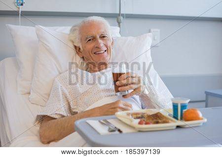 Senior patient eating his lunch on a tray in hospital and looking at camera. Portrait of old man eating a healthy meal in hospital room. Aged man enjoying meal in hospital while lying on bed.