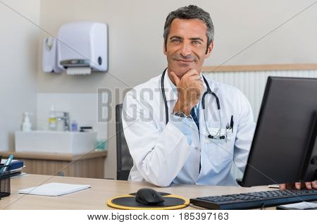 Portrait of a happy senior doctor sitting at desk. Mature confident doctor using computer in his office. Successful man doctor looking at camera.