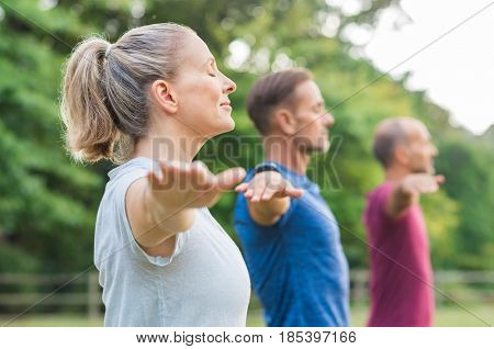 Group of senior people with closed eyes stretching arms at park. Happy mature people doing yoga exercise outdoor on a bright morning. Yoga class with woman and men doing breath exercise.