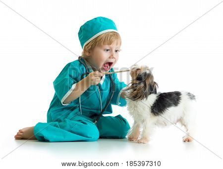 Say aaah - child weared doctor clothes playing veterinarian checking teeth of dog