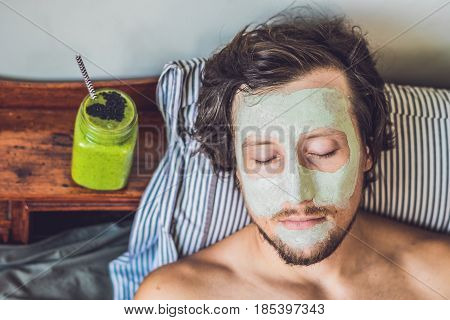 Spa Man Applying Facial Green Clay Mask. Beauty Treatments. Fresh Green Smoothie With Banana And Spi