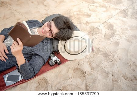 happy young Asian man with jean shirt and glasses lying on sandy beach reading his notebook and smiling vacation time and summer holiday concepts