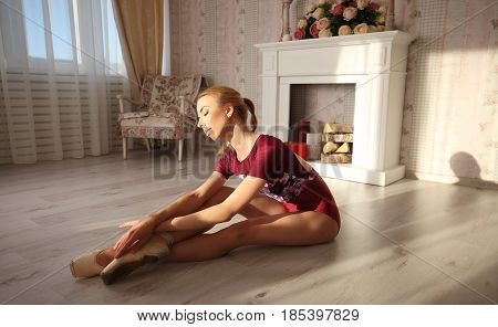 Beautiful Graceful Young Ballerina In Pointe Shoes On Wooden Floor Makes Ballet Leg Stretching.