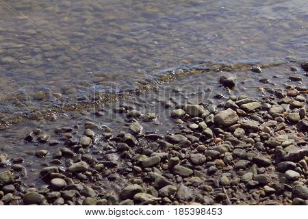 A very small wave moving up onto a pebble shore