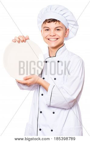 Cheerful handsome teen boy wearing chef uniform. Portrait of a happy cute male child cook with blank plate for menu, isolated on white background. Food and cooking concept.