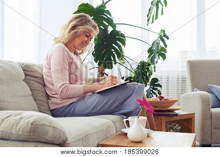 Mid shot of attractive adult woman smiling and writing letter while sitting on sofa