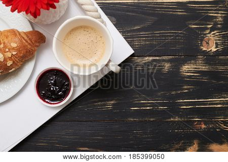 Cropped shot of french breakfast with croissant on service tray. Croissant with cup of coffee, and jam