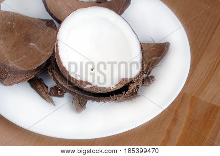 Still life with broken coconut shell ripe white flesh inside and debris on round white plate on brown wooden table horizontal close up photo