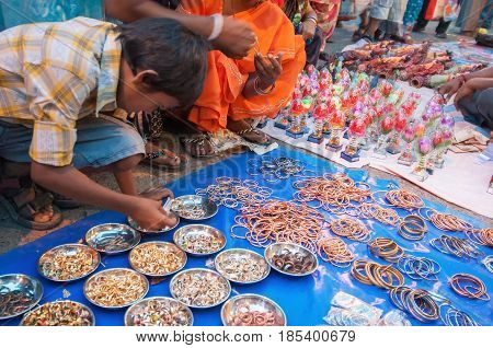 KOLKATA WEST BENGAL INDIA - 12TH AUGUST 2012 : Indian girl child choosing ornament products from out door local market place. India is boomimg with middle class consumers in society.