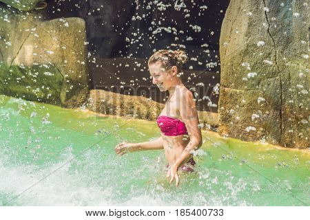 Young Woman Relaxing Under A Waterfall In Aquapark
