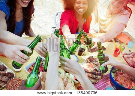 group of diverse people at garden lunch table toasting cheers with bottles of beer. custom colors and sunshine effects.. concept of multi-racial friendship youth togetherness and people having fun